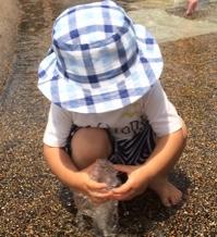 小さい噴水で遊ぶ1歳児